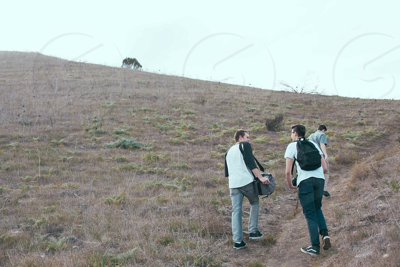 3 men walking on mountain photo