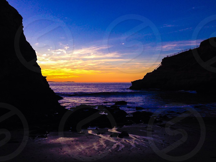 yellow and blue sunset sky over black rock cliffs to beach inlet photo