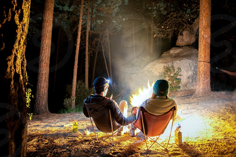 A couple wearing jackets sits at a campfire during the night. Chairs flames dirt trees beanies cold smoke photo