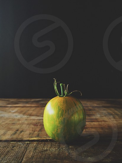 green melon on a wood table photo