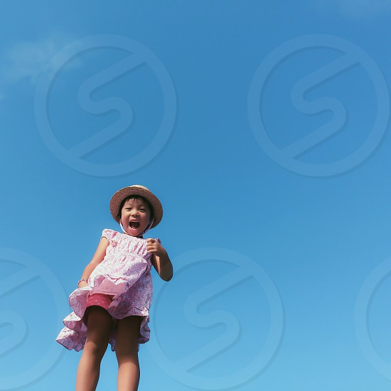 girl with short black hair wearing tan hat and pink dress standing under clear blue sky at daytime photo