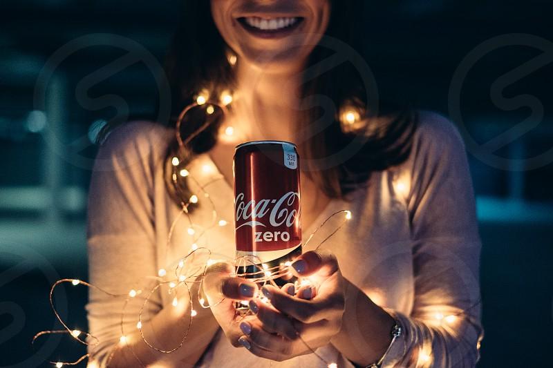 Smiling woman holding coca-cola photo