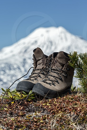 Old tourist boots on background volcano on Kamchatka Peninsula. Far East Russia. photo