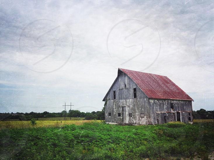 grey barn on green field  photo