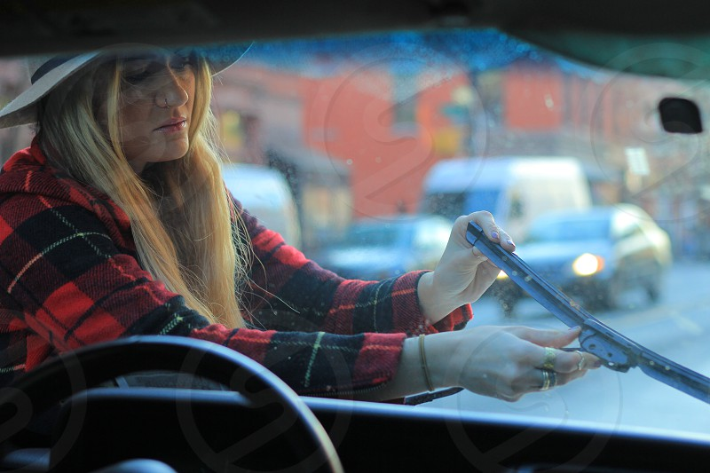 woman in black and red plaid long sleeved shirt fixing car wiper photo