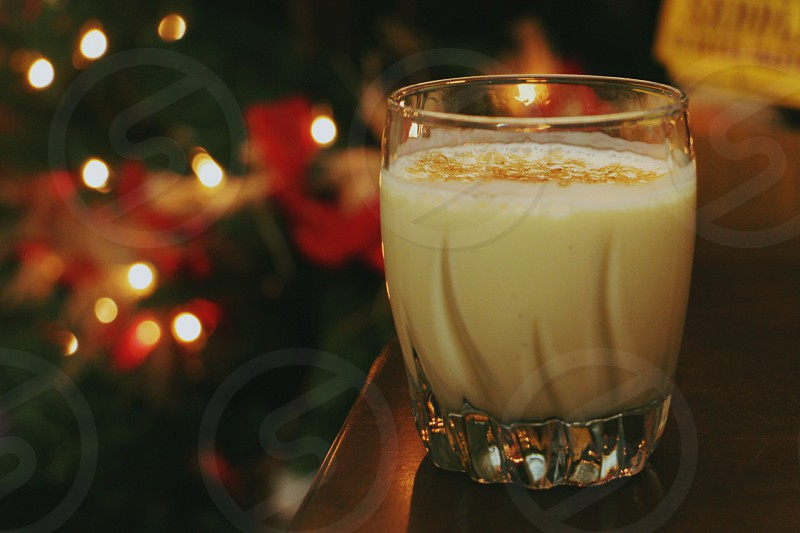 white cream in clear drinking glass near christmas tree photo
