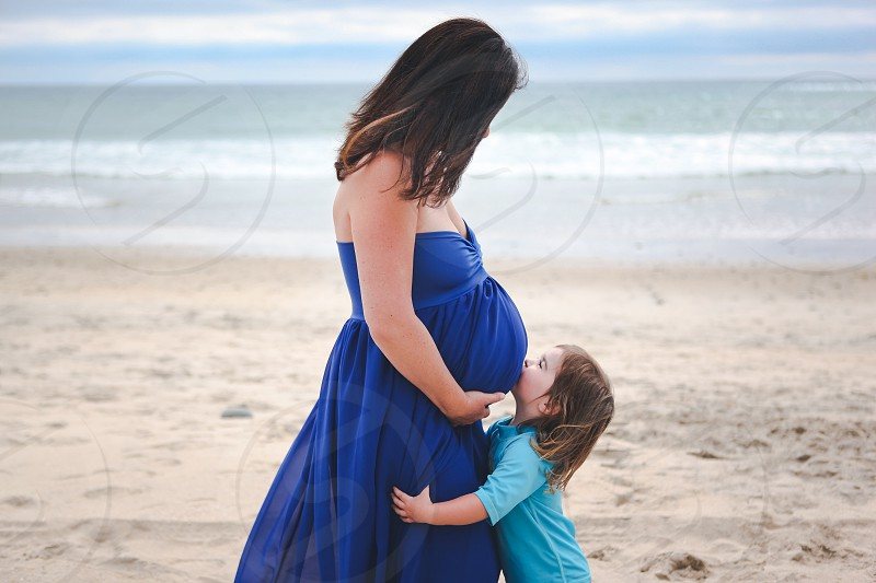 brunette pregnant woman in a strapless blue dress looking down at a toddler in a blue shirt on a beach photo