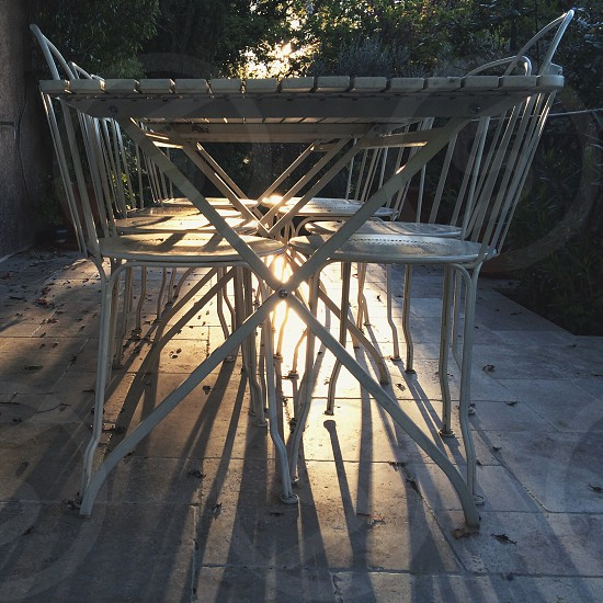 white metal garden chairs and brown wooden table photo