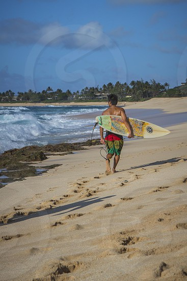 man on sea shore carrying white and green surf board photo