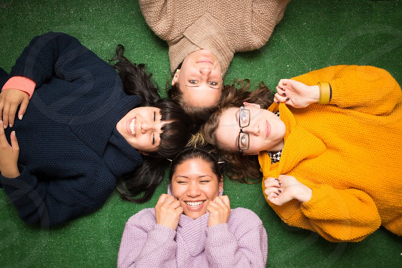 4 women lying on green flooring photo
