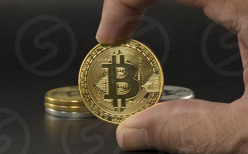 hand showing lbitcoin with black background with a single litecoin facing the camera in sharp focus with shading on the icon letter B on the face of the bit coin photo