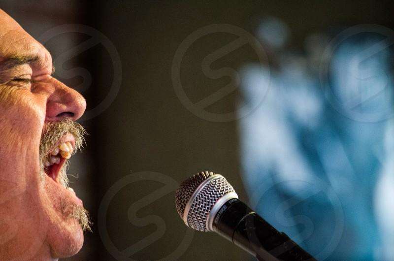 closeup photo of man singing on black microphone photo