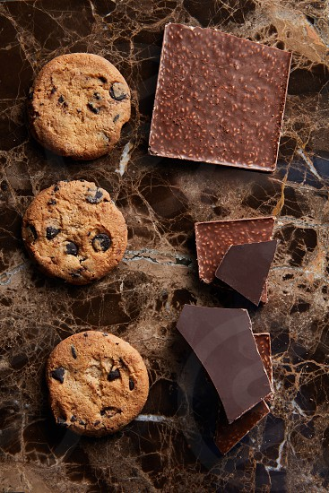 pieces of chocolate and cookies with chocolate Drops on a dark marble background photo
