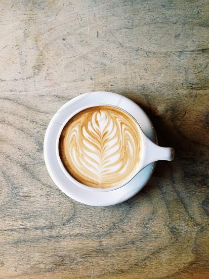 ceramic cup of cappucino with design photo