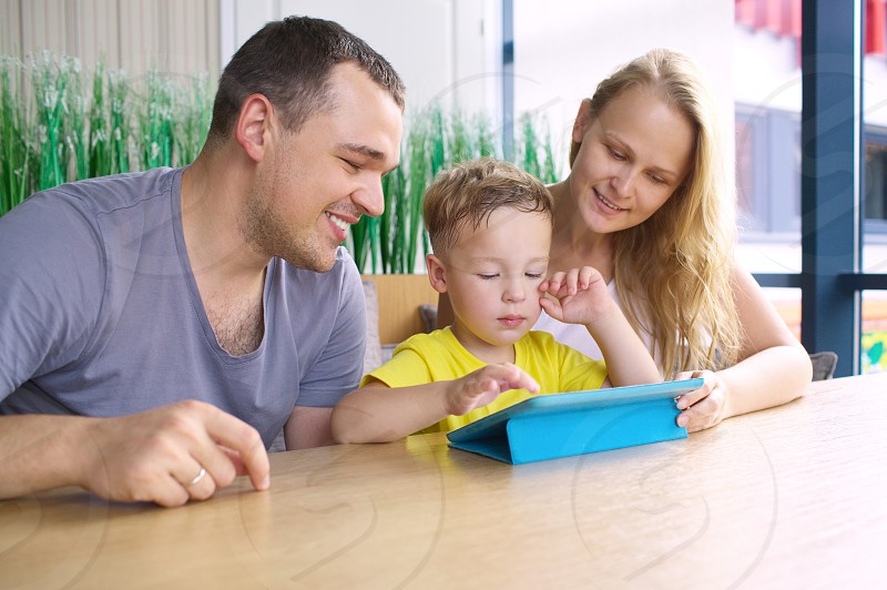 Family with child in cafe. Mother and father watching son playing on touch pad photo