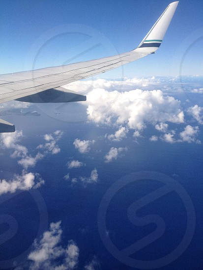 right airplane wing above cumulus clouds and blue seawater photo