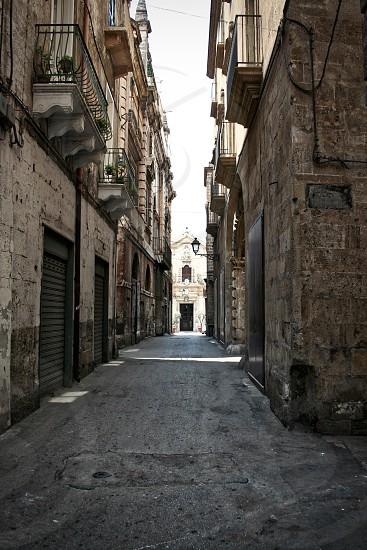 alley in between brown bricked buildings photo