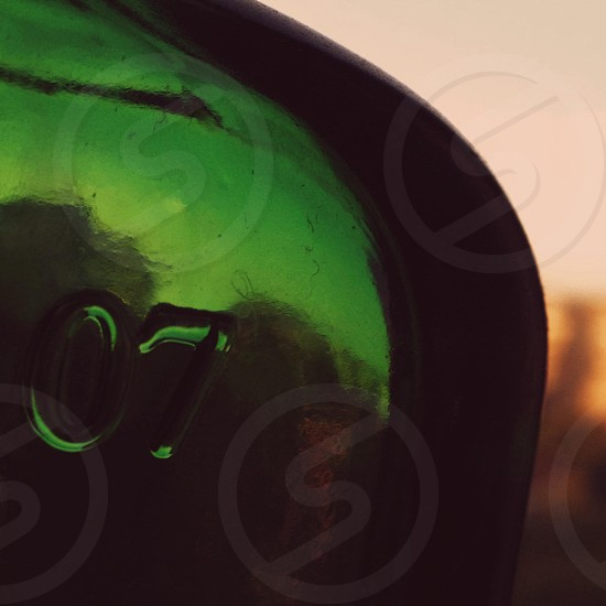 """The green glass bottle with sign """"07"""" on blurred evening city background photo"""