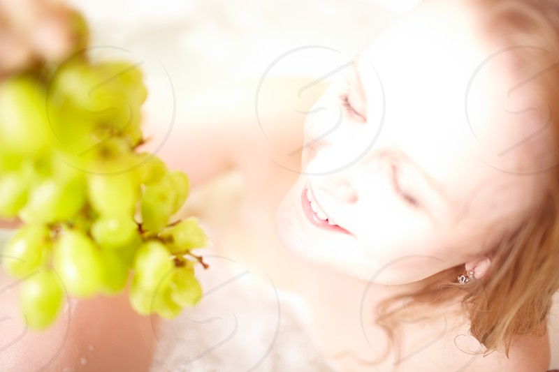 Girl in the bathroom with grapes spa-style image. Shallow dof. photo