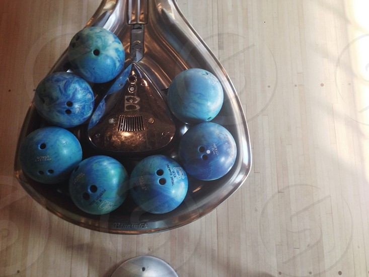 seven blue bowling balls in ball release ramp photo