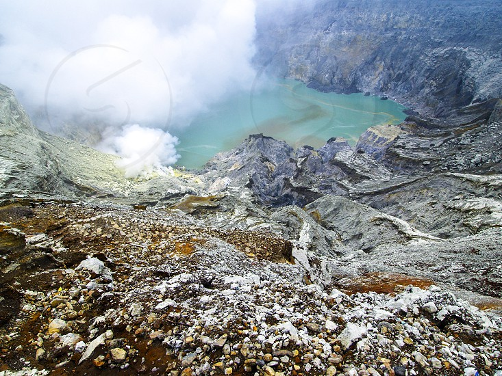 The sulphuric lake of Kawah Ijen Mountain's cauldron in the Ijen volcano complex a group of composite volcanoes in the Banyuwangi Regency of East Java Indonesia. photo