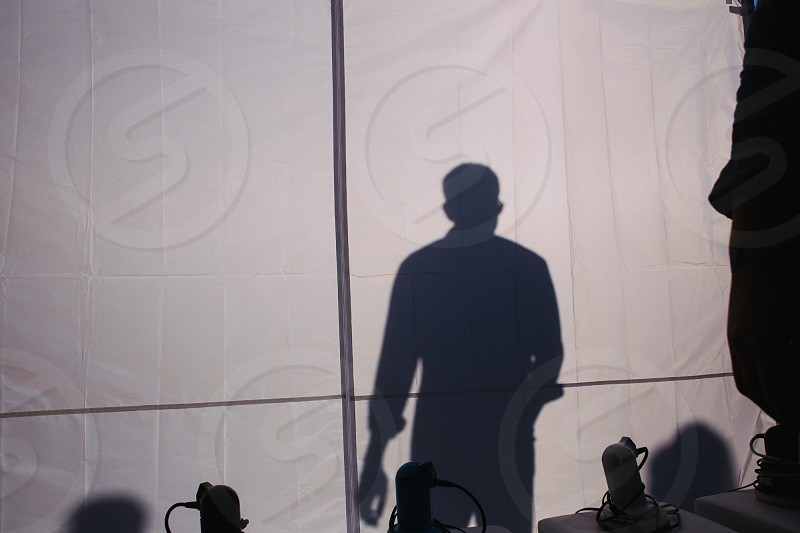 black shadow of man on white fabric surface photo