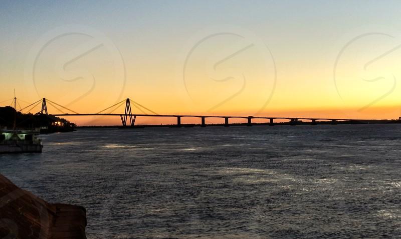 sunset behind a bridge across the parana river photo