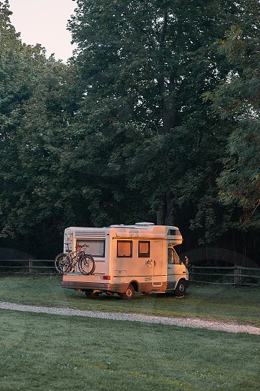 Camper van parked on camping in forest at sunrise during vacation journey. Candid people real moments authentic situations photo