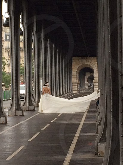 woman in white wedding gown taking photo in hallway photo