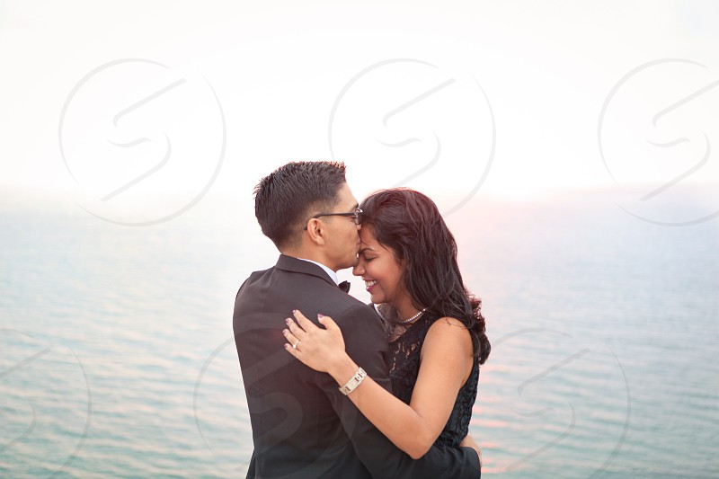 man wearing black blazer kissing the forehead of woman wearing black sleeveless dress smiling in front of green calm of water during daytime photo