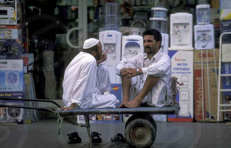 two transport worker in the souq or Market in the old town in the city of Dubai in the Arab Emirates in the Gulf of Arabia. photo