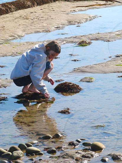 Tidepooling shell rock teen girl beach sand water photo
