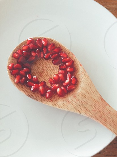 red fruits on brown spoon photo