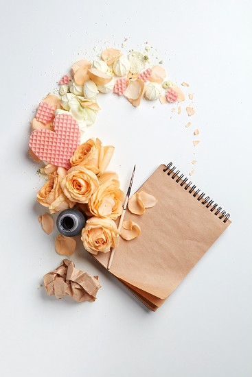 Inkwell with a notebook and a heart with flowers on a white background with space for text photo