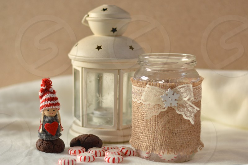 Lantern doll with a heart and a jar of candy and biscuits photo