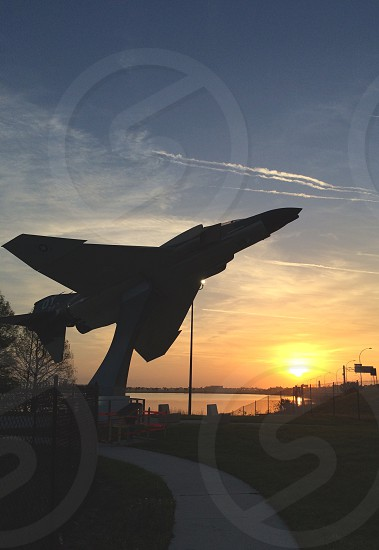 fighter jet on green grass during sunset photo