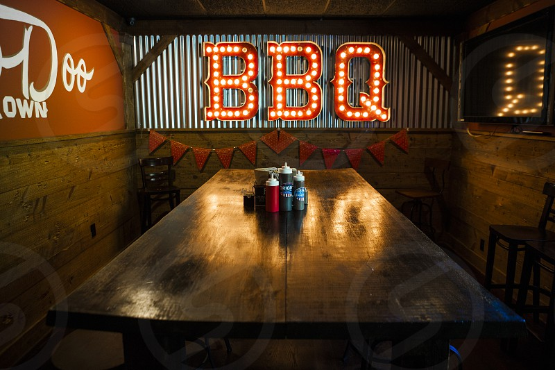 bbq neon signage in front of brown wooden table with condiment shaker top photo