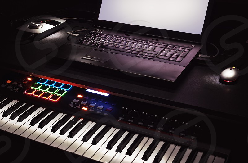 Mini home studio midi controller and laptop on table. photo