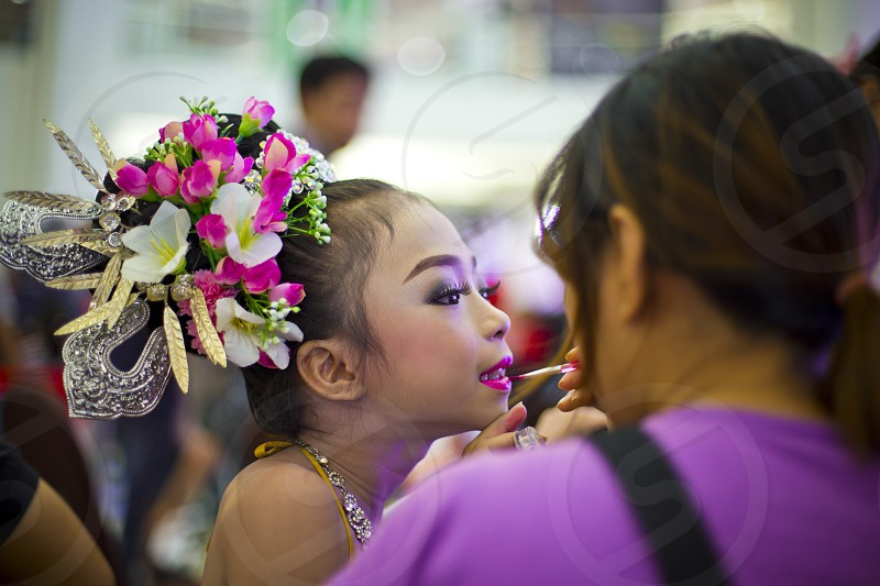 Mother applying make up on her daughter lips while preparing for the show kid children showtime cosmetics lipstick eyelash eyes leash hairstylestylist  pretty girl mother and daughter prepared benbdprod photo