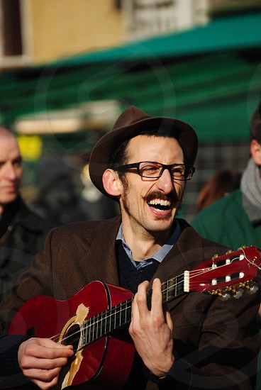 man playing red acoustic guitar photo