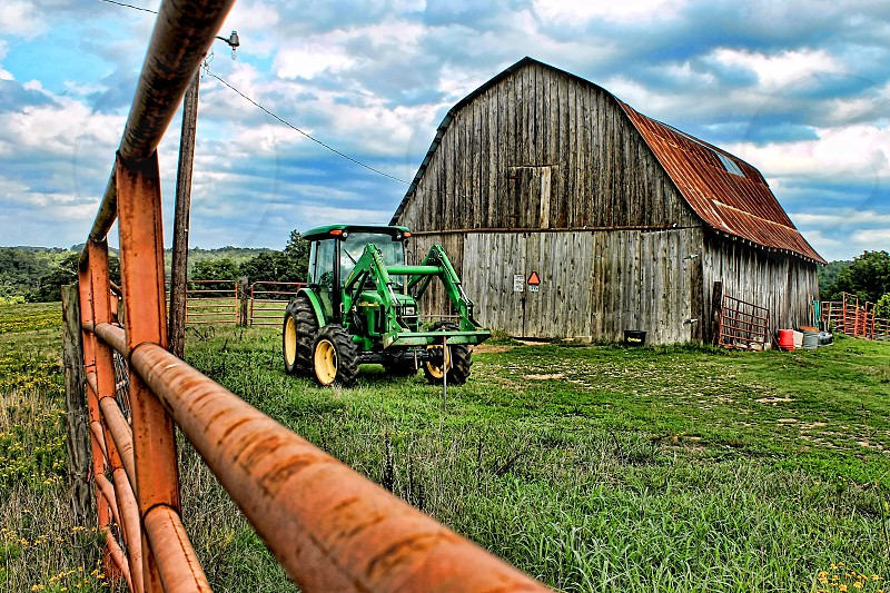 Old barn and green tractor is surrounded by a red metal fence on a farm. photo