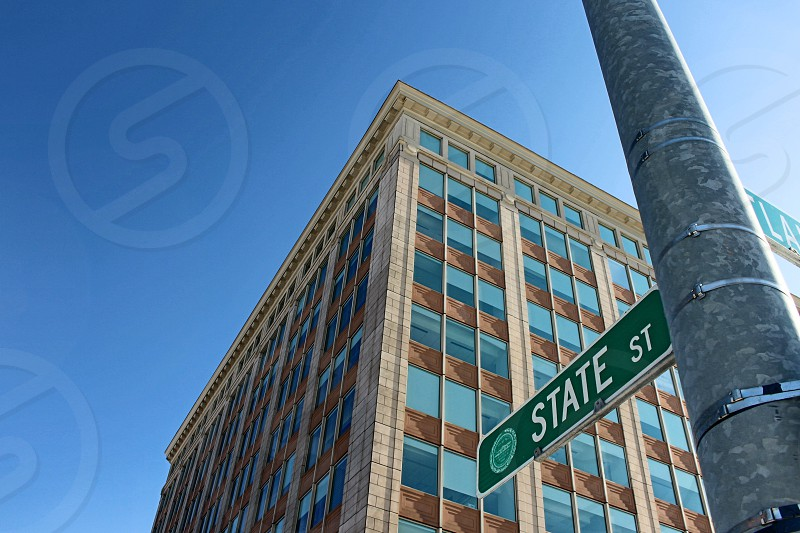 beige and brown high rise building on state street under blue sky during daytime photo