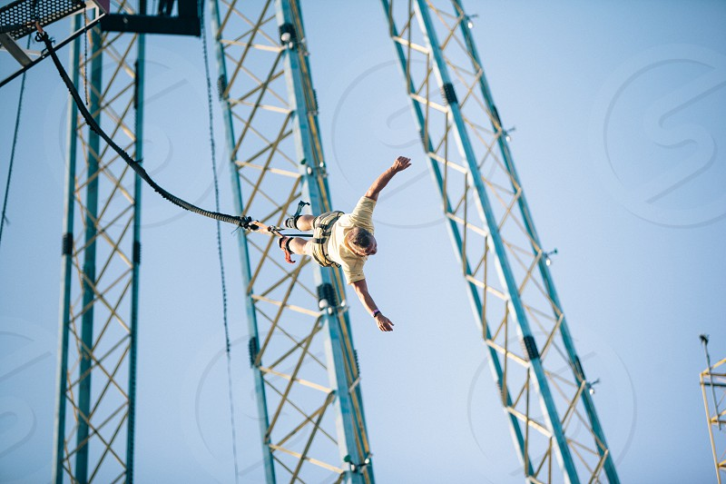 man in yellow shirt playing bungee jumping under blue sky in closeup photography photo