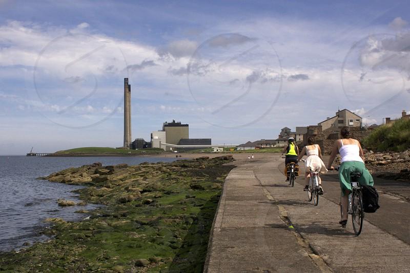 Three women biking under blue skies along a coastal path in Scotland. photo