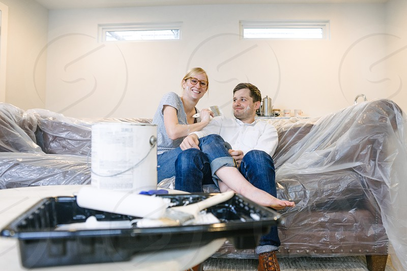Young couple having fun renovating their home playing with paint. photo