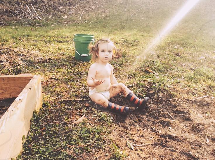 girl sitting on brown soil photo