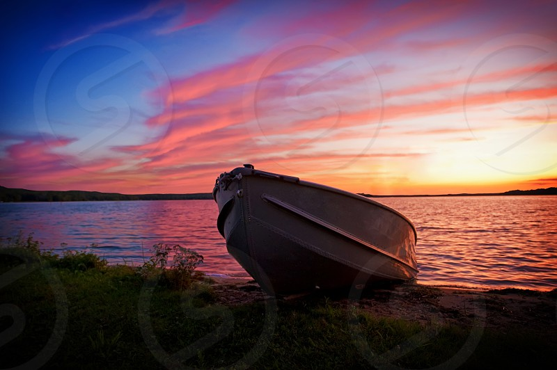 Fishing boat on shore at sunset with lake in background photo