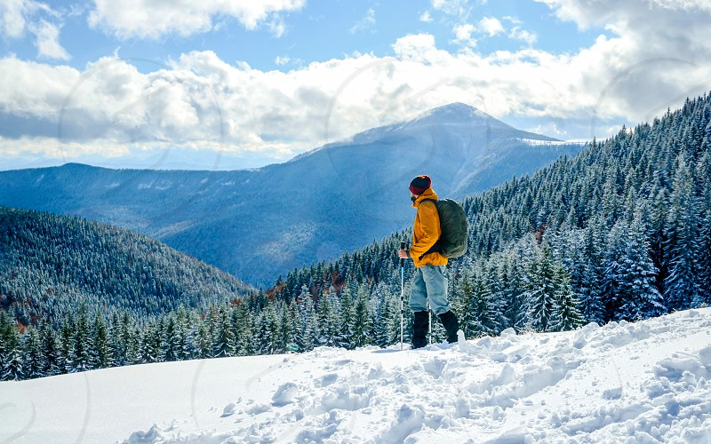 hiker with a backpack in snowy mountains travel health success concept photo