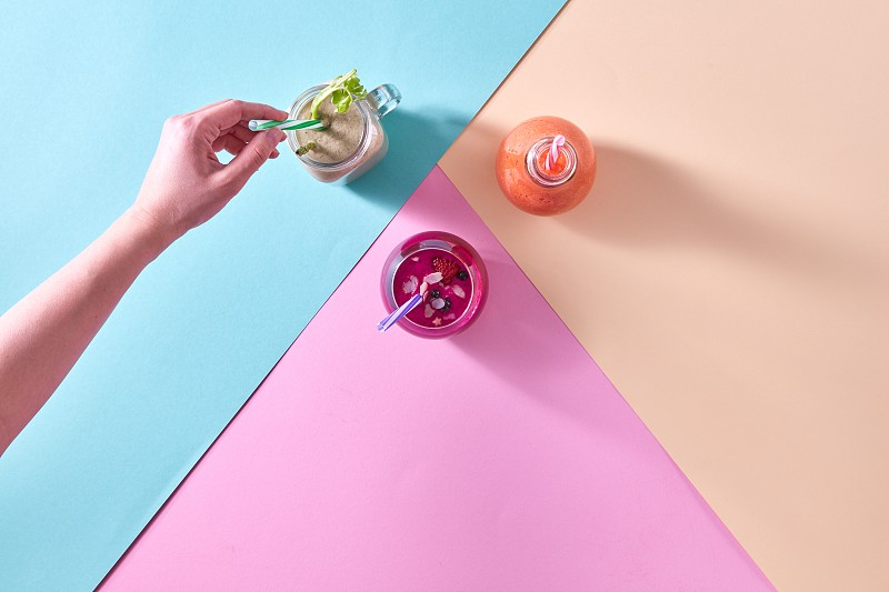 Top view of juices smoothie of summer fruits and berries - strawberry raspberry blueberry blackberry kiwi and a woman's hand put a drinking straw on a colored paper background  copy space photo