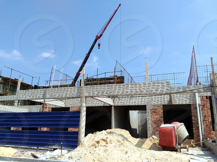 grey and brown bricks wall building frame with black and red tower crane under white and blue sky during daytime photo